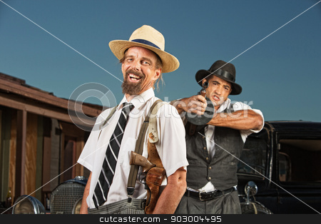 Easygoing Gangster with Guard stock photo, Easygoing vintage mobster with guard aiming gun by Scott Griessel