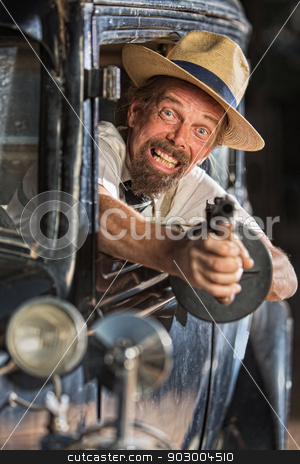 Bearded Gangster Shooting From Car stock photo, Bearded man firing submachine gun from vintage 1920s car by Scott Griessel