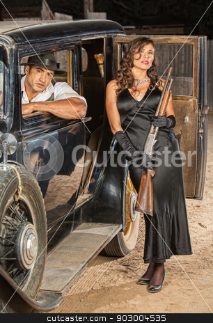 Gangster Pair with Shotgun in Car stock photo, Male and female retro gangsters with shotgun in car by Scott Griessel
