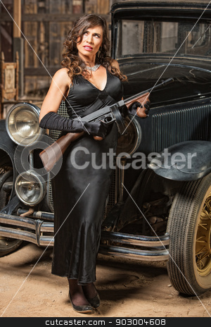 Lady with Gun Looking Away stock photo, Beautiful woman with vintage machine gun looking away by Scott Griessel