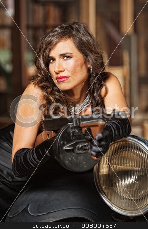 Smirking Woman with Machine Gun stock photo, Smirking woman in black dress holding submachine gun by Scott Griessel