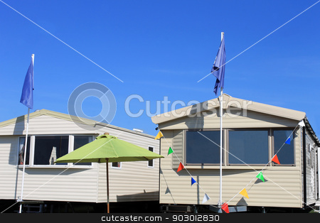 New caravans on trailer park stock photo, Exterior of two new caravans on trailer park with blue sky background. by Martin Crowdy