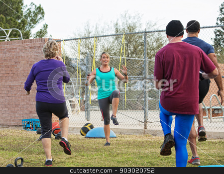 Mature Fitness Instructor Teaching stock photo, Female fitness instructor leading group of mature adults by Scott Griessel