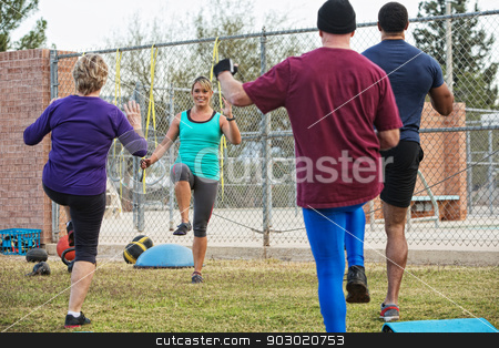 Woman Leading Four Adults in Exercise stock photo, Active adults with instructor performing boot camp exercises by Scott Griessel