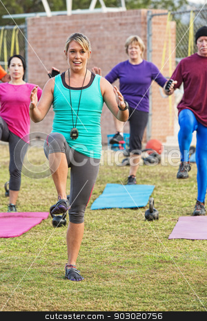 Smiling Workout Instructor stock photo, Smiling workout instructor with diverse group outdoors by Scott Griessel