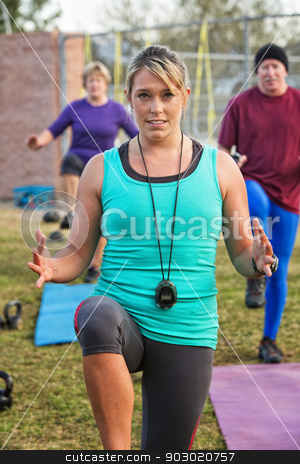 Fit Woman Teaching Group stock photo, Fit woman with stopwatch exercising in front of group by Scott Griessel