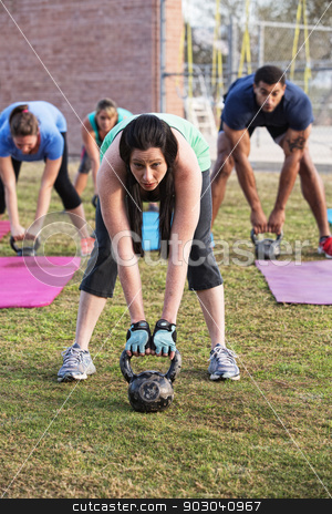 Adults Lifting Kettle Bell Weights stock photo, Beautiful woman leading group with kettle bell weights by Scott Griessel