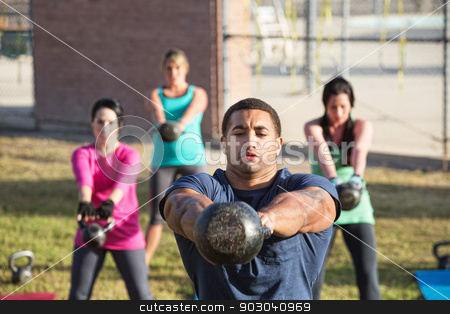 Four People Using Weights stock photo, Four people exercising in outdoor boot camp with kettle bells by Scott Griessel