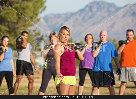 Large Group Working Out stock photo, Serious woman with people exercising in outdoor boot camp by Scott Griessel
