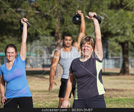 Middle Aged Woman Lifting Weights stock photo, Mature white female exercising with kettle bell weights by Scott Griessel