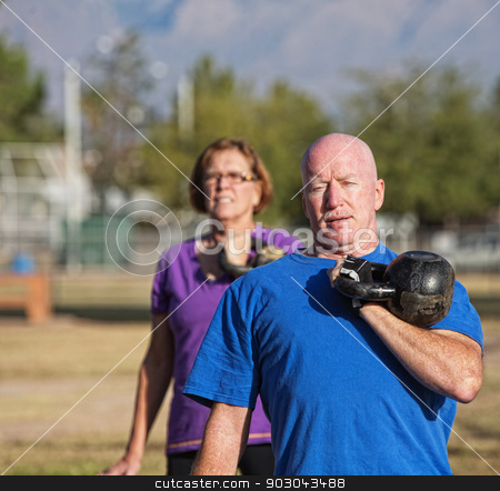 Athletic Mature Man Lifting Weights stock photo, Athletic middle aged man lifting kettle bell weight by Scott Griessel