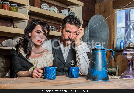 Sad Western Sheriff and Woman Pose Inside House  stock photo, Upset Western Sheriff Poses With a Woman Inside of a House by Scott Griessel