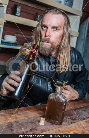Drunk Western Man at Table stock photo, Drunk Western Man Aims Gun Towards Bottle as he Sits at Table by Scott Griessel