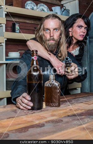Crazed Western Man With Woman at Table stock photo, Crazed Western Man Aims Gun Towards You as he Sits at Table With Woman by Scott Griessel