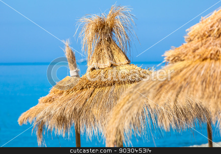 Straw umbrella hats stock photo, Yellow straw umbrella hats against blue sky-water background. Focus on the central hat by Natalia Macheda
