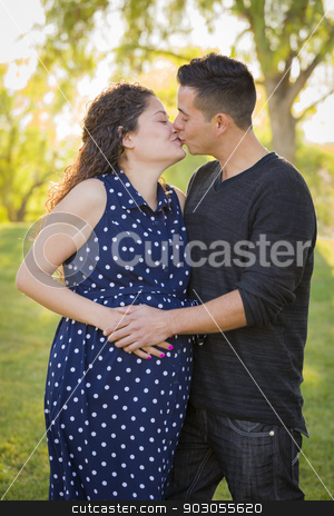 Hispanic Man Kisses His Pregnant Wife Outdoors At the Park stock photo, Hispanic Man Kisses His Pregnant Wife and Feels Their Baby Kick Outdoors At the Park. by Andy Dean