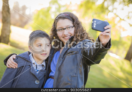 Brother and Sister Taking Cell Phone Picture of Themselves stock photo, Brother and Sister Taking Cell Phone Picture of Themselves Outdoors At The Park. by Andy Dean