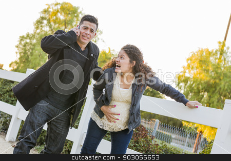 Pregnant Woman In Pain While Husband Uses Cell Phone Outside stock photo, Pregnant Woman In Pain with Hand on Her Belly While Husband Uses Cell Phone Outside. by Andy Dean