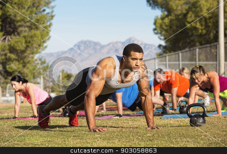 Strong Man Doing Push-Ups stock photo, Strong man leading push-ups with exercise group by Scott Griessel