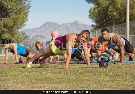 Group Doing Push-Ups with Instructor stock photo, Cheerful blond fitness instructor leading group in push-ups by Scott Griessel