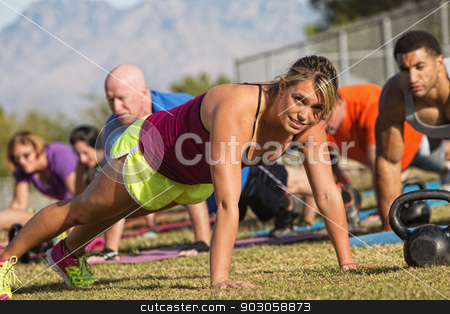 Enthusiastic Woman Doing Push-Ups stock photo, Pretty European woman doing push-ups with group outdoors by Scott Griessel