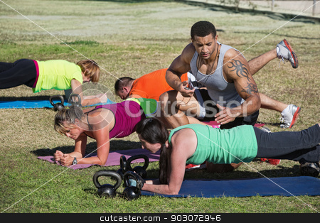 Fitness Instructor Timing Students  stock photo, Muscular instructor with stopwatch helping students in fitness class by Scott Griessel
