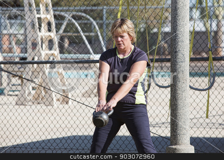 Middle Aged Woman Lifting Weights stock photo, Middle aged woman lifting kettle bell weights outdoors by Scott Griessel