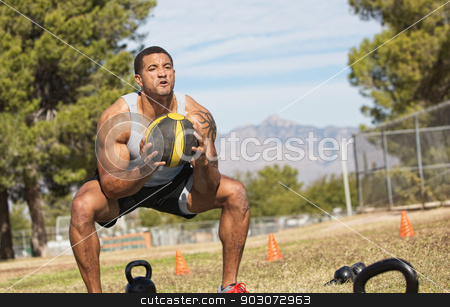 Man Using Medicine Ball stock photo, Strong African man squatting with medicine ball by Scott Griessel