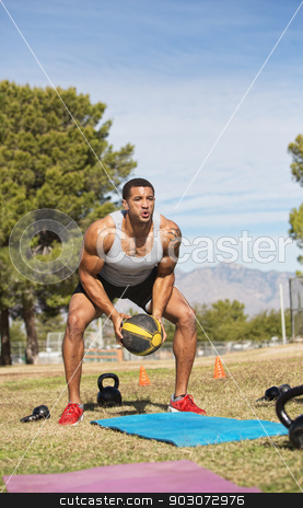 Male Exercising with Medicine Ball stock photo, Single man squatting and lifting medicine ball by Scott Griessel