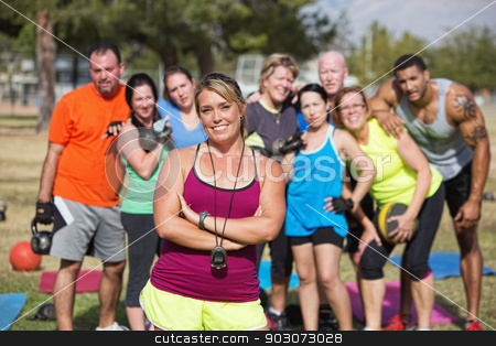 Confident Trainer with Fitness Class stock photo, Smiling confident trainer standing with fitness class by Scott Griessel