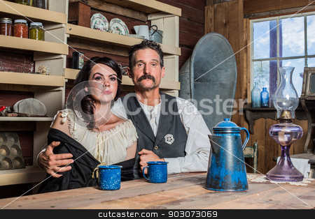 Deadpan Western Sheriff and Woman Pose Inside House  stock photo, Western sheriff poses with a woman for a portrait inside a house by Scott Griessel