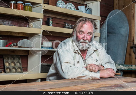Solemn Western Man at Table stock photo, Solemn western man looks towards you as he sits at table by Scott Griessel