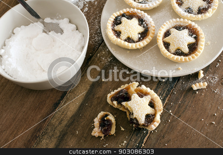 Eating delicious fresh baked Christmas mince pies stock photo, Eating delicious freshly baked Christmas mince pies decorated with pastry stars and sprinkled with icing sugar, one half eaten pie with crumbs in the foreground by Stephen Gibson