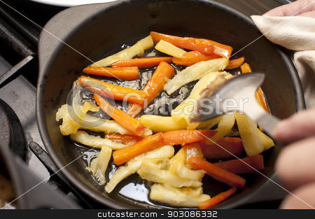 Carrot and parsnip batons being sauteed stock photo, Fresh winter carrot and parsnip batons being sauteed in a metal skillet with a hand holding a spoon above them by Stephen Gibson