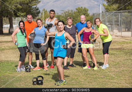 Cute Woman Posing with Fitness Group stock photo, Cute Latino female lifting weights with fitness group by Scott Griessel