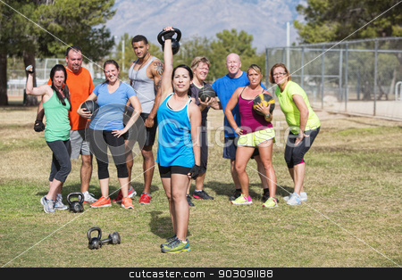 Smiling Woman Exercising stock photo, Happy woman lifting weights with group outdoors by Scott Griessel