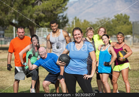 Confident Fit Woman with Group stock photo, Smilng woman and boot camp fitness group with medicine ball by Scott Griessel