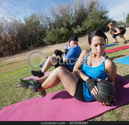 Latino Woman Doing Sit-Ups stock photo, Active diverse group in boot camp fitness class on mats by Scott Griessel