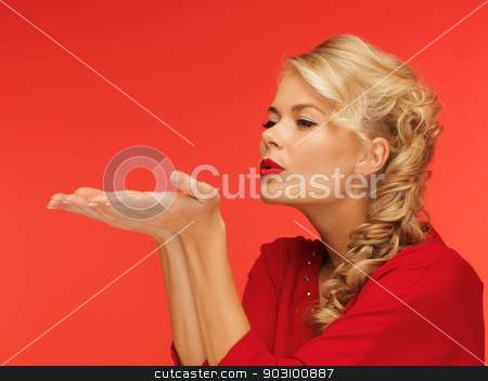 woman blowing something on the palms of her hands