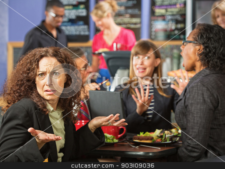 Irritated Woman in Cafe stock photo, Irritated business woman with coworkers in cafeteria by Scott Griessel