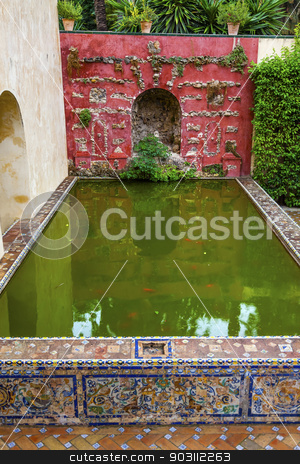 Green Pool Reflection Mosaic Wall Garden Alcazar Royal Palace Se stock photo, Green Pool Basin Reflection Mosaic Wall Garden Alcazar Royal Palace Seville Andalusia Spain.  Originally a Moorish Fort, oldest Royal Palace still in use in Europe. Built in the 1100s and rebuilt in the 1300s.  by William Perry