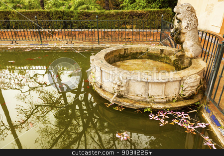 Lion Pool Fountain Garden Alcazar Royal Palace Seville Spain stock photo, Lion Statue Fountain Pool Reflection Fish Flowers Garden Alcazar Royal Palace Seville Andalusia Spain.  Originally a Moorish Fort, oldest Royal Palace still in use in Europe. Built in the 1100s and rebuilt in the 1300s.  by William Perry