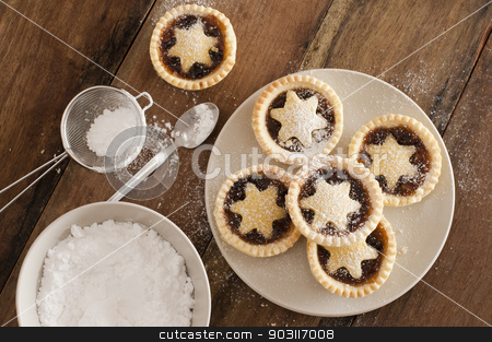 Traditional Christmas fruit mince pies stock photo, Traditional Christmas fruit mince pies decorated with pastry stars on a kitchen table ready to be sprinkled with powdered icing sugar in a sieve for a delicious seasonal teatime snack, overhead view by Stephen Gibson