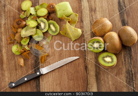 Peeling and dicing kiwifruit for dessert stock photo, Overhead view of a wooden kitchen counter with a knife and fresh kiwi fruit that are being peeled and diced for a healthy delicious tropical dessert by Stephen Gibson