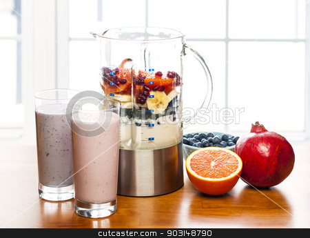 Making smoothies in blender with fruit and yogurt stock photo, Prepared smoothies and healthy smoothie ingredients in blender with fresh fruit ready to blend on kitchen table by Elena Elisseeva