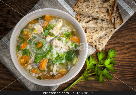 Chicken soup with rice and vegetables stock photo, Chicken rice soup with vegetables in bowl and bread from above by Elena Elisseeva