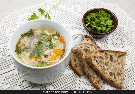 Cup of chicken rice soup stock photo, Cup of hot chicken rice soup served with bread and parsley on crochet tablecloth by Elena Elisseeva