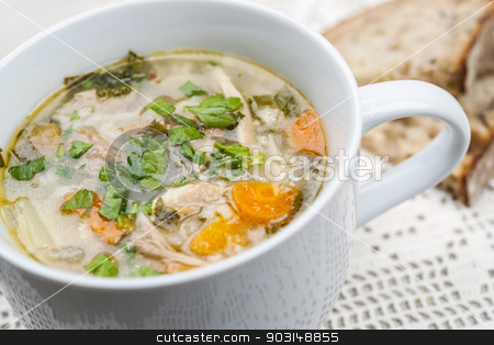 Cup of chicken rise soup stock photo, Cup of hot chicken rice soup served with bread on crochet tablecloth closeup by Elena Elisseeva