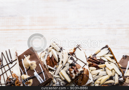 Chocolate bark on wood background stock photo, Assorted chocolate caramel bark pieces arranged on wooden background from above with copy space by Elena Elisseeva