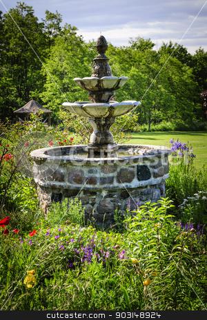 Garden with fountain stock photo, Lush green garden with tiered stone fountain by Elena Elisseeva